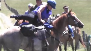 Notice the rider holds both the saddle horn and reins with the right hand.