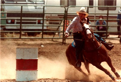 A barrel racer leans into the turn